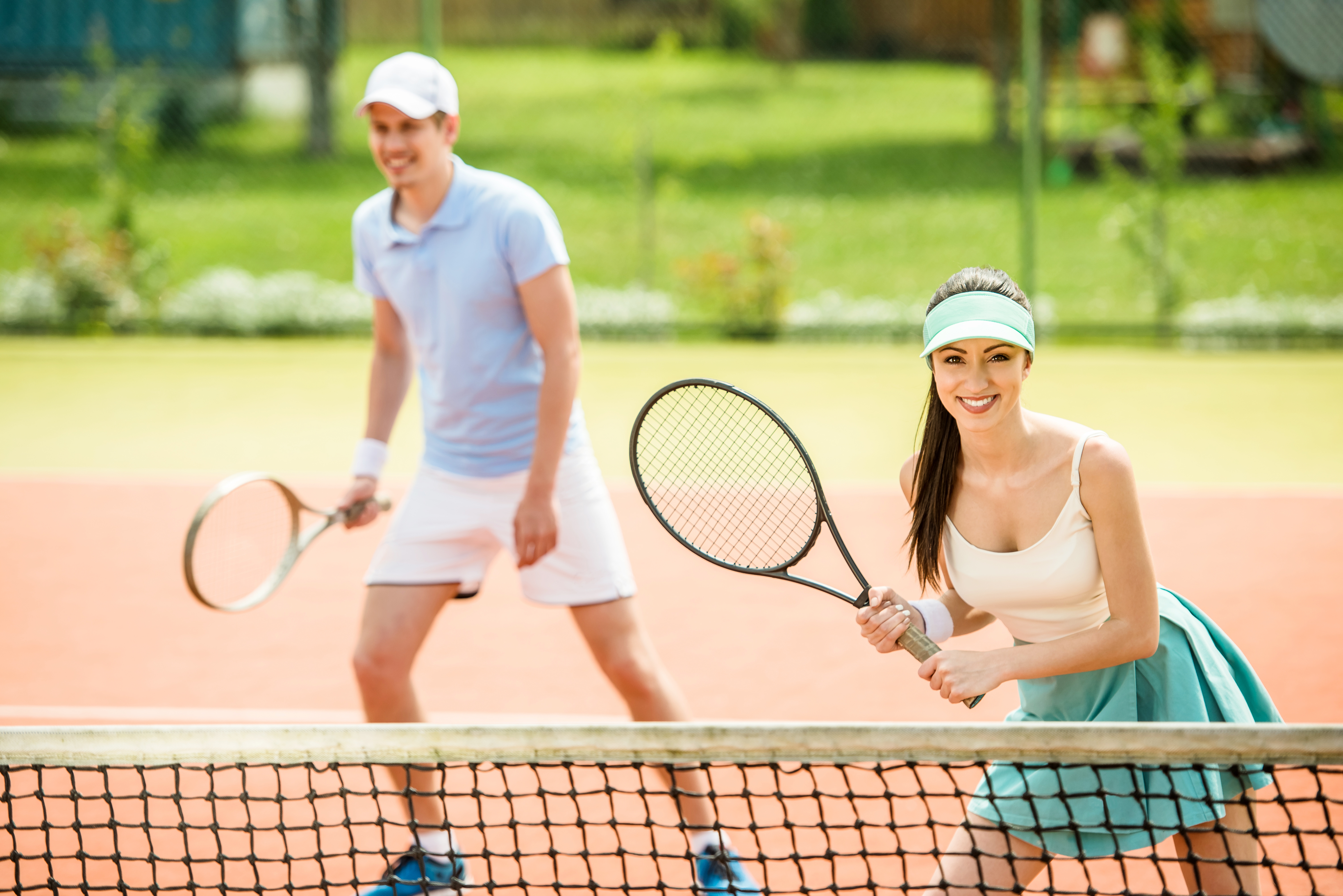 Couple,Playing,Doubles,At,The,Tennis,Court.